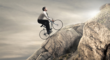 A man riding bicycle up the hill
