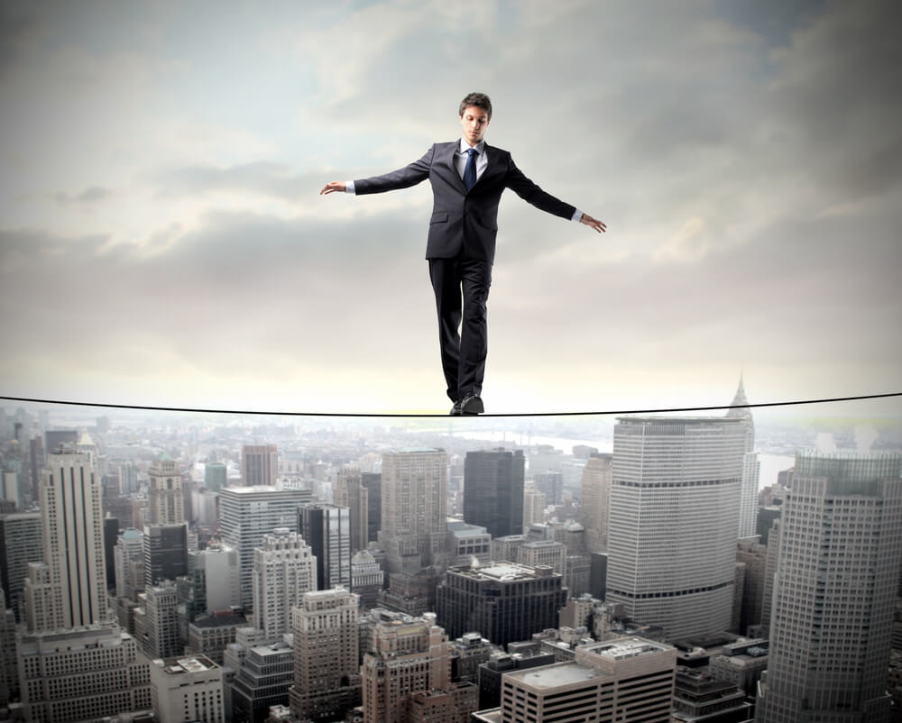 A business man walking on a thin rope, above a canyon which is the city
